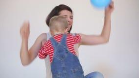 Jonge moeder en jong geitje en zoon die dansen spelen stock video