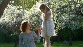 Jonge moeder en leuke dochter in mooie bloesemtuin Langzame Motie stock videobeelden