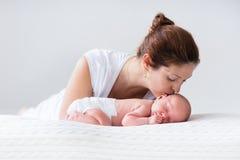 Jonge moeder en pasgeboren baby in witte slaapkamer Stock Foto