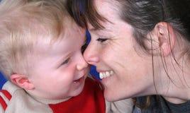 Jonge moeder en peuterzoon die een grap samen deelt. Stock Foto's