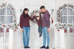 Jonge moeder en vader die kind omhoog op portiek van Kerstmis h opheffen royalty-vrije stock afbeeldingen