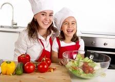 Jonge moeder en weinig dochter die bij huiskeuken salade voor lunch voorbereiden die schort en kokhoed dragen Stock Foto