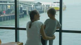 Jonge moeder en weinig dochter die een reis wachten bij zeehavenzitkamer stock video