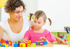 Jonge moeder en weinig dochter die met stuk speelgoed blokken spelen Royalty-vrije Stock Foto's