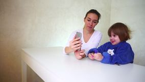 Jonge moeder en weinig dochter die met telefooncamera spelen, meisjes die en grappige cameragevolgen zitten gebruiken stock video