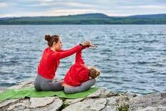 Jonge moeder en weinig dochter die yogaoefeningen op de steen doen dichtbij rivier Royalty-vrije Stock Fotografie
