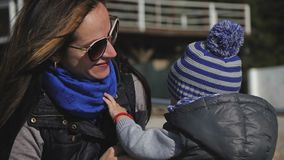 Jonge moeder en weinig kind, haar zoon die in de winterkleren spelen stock footage