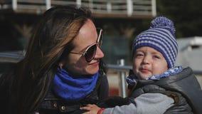 Jonge moeder en weinig kind, haar zoon die in de winterkleren spelen stock video