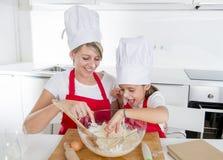 Jonge moeder en weinig zoete dochter in kokhoed en schort die thuis samen het bakken van keuken koken stock foto's