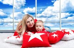 Jonge moeder en weinig zoon spelen die op het hoofdkussen liggen Het concept een familievakantie Mooie kussens voor huis binnenla Stock Afbeeldingen