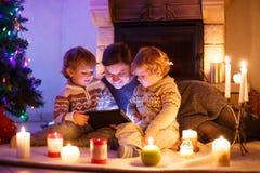 Jonge moeder en zijn kleine kinderen die door een open haard op C zitten royalty-vrije stock afbeelding