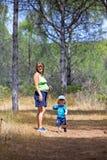 Jonge moeder en zoon die door hout lopen Stock Foto's