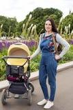 Jonge moeder in het park op een gang met een klein kind in een wandelwagen Royalty-vrije Stock Fotografie