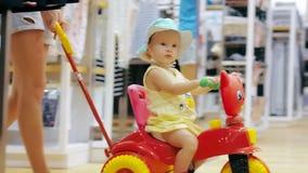 Jonge moeder in kledingsopslag met weinig dochter op de fiets van kinderen stock videobeelden