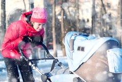 Jonge moeder met baby in de winter Stock Afbeelding