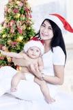 Jonge moeder met baby met santahoeden Stock Foto's
