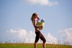 Jonge moeder met baby op een gebied Royalty-vrije Stock Afbeelding