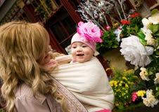 Jonge moeder met babydochter in een tuin royalty-vrije stock afbeeldingen