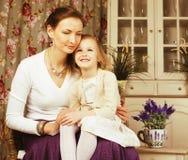 Jonge moeder met dochter thuis wit helder binnenland Stock Afbeeldingen