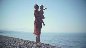 Jonge moeder met een baby die in hun handen op het strand lopen De baby glimlacht en golft bij de camera stock videobeelden