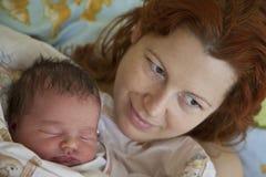 Jonge moeder met een babyzuigeling Royalty-vrije Stock Foto's