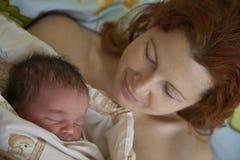 Jonge moeder met een babyzuigeling Stock Foto