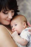 jonge moeder met haar baby in haar wapens Royalty-vrije Stock Foto's