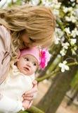 Jonge moeder met haar babydochter in een tuin Stock Afbeelding