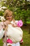 Jonge moeder met haar babydochter in tuin royalty-vrije stock afbeeldingen