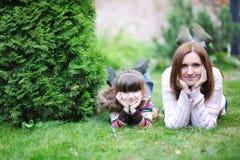 Jonge moeder met haar dochter in de tuin stock afbeeldingen