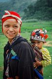 jonge moeder met haar leuk kind naast een padieveld omhoog hoog in de nevelige bergen stock afbeelding