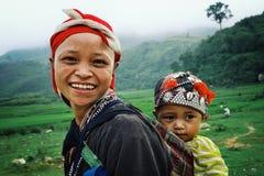 jonge moeder met haar leuk kind naast een padieveld omhoog hoog in de nevelige bergen royalty-vrije stock fotografie