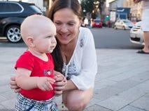 Jonge moeder met haar peuterzoon die in openlucht in stad spelen royalty-vrije stock fotografie