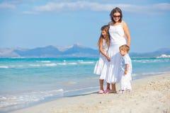 Jonge moeder met haar twee jonge geitjes op strandvakantie royalty-vrije stock afbeeldingen