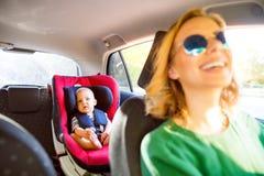 Jonge moeder met haar weinig babyjongen in de auto stock fotografie