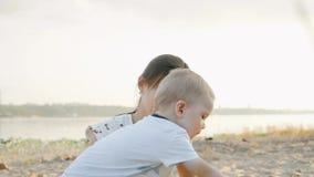 Jonge moeder met haar jonge zoon op het strand bij zonsondergang Langzame Motie stock footage