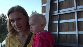 Jonge moeder met haar zuigelingsbaby die op de treden van de observatietoren in aard beklimmen Handbediend 4K stock video