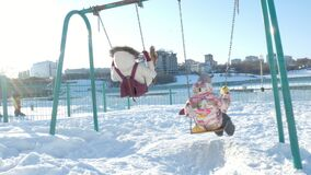 Jonge moeder met kind het slingeren op schommelings vastgestelde openlucht in de winterpark Sneeuw die, sneeuwval, de wintertijd