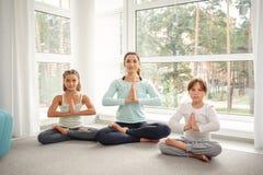 Jonge moeder met kinderen die thuis mediteren Stock Foto's