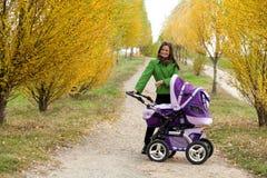 Jonge moeder met kinderwagen Stock Foto's