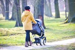 Jonge moeder met kinderwagen Stock Foto