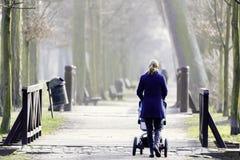 Jonge moeder met kinderwagen Royalty-vrije Stock Afbeeldingen