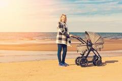 Jonge moeder met kinderwagen op het strand Royalty-vrije Stock Afbeelding