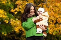 Jonge moeder met omhoog baby in wapens Stock Afbeelding
