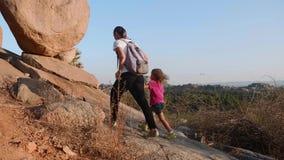 Jonge moeder met weinig dochter die bij sleep in bergen lopen stock video