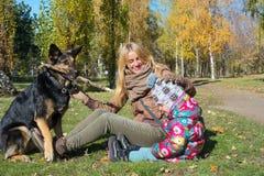 Jonge moeder met weinig dochter die met hond spelen Royalty-vrije Stock Fotografie