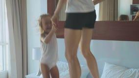 Jonge moeder met weinig dochter die op bed samen bij de ochtend springen stock videobeelden
