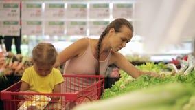 Jonge moeder met weinig dochter in karretje die greens selecteren bij supermarkt stock footage