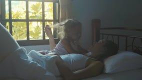 Jonge moeder met weinig leuke dochter in bed na het awaking stock video