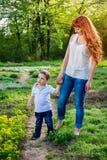 Jonge moedergangen met haar weinig zoon in de tuin De dagconcept van de moeder ` s royalty-vrije stock afbeeldingen
